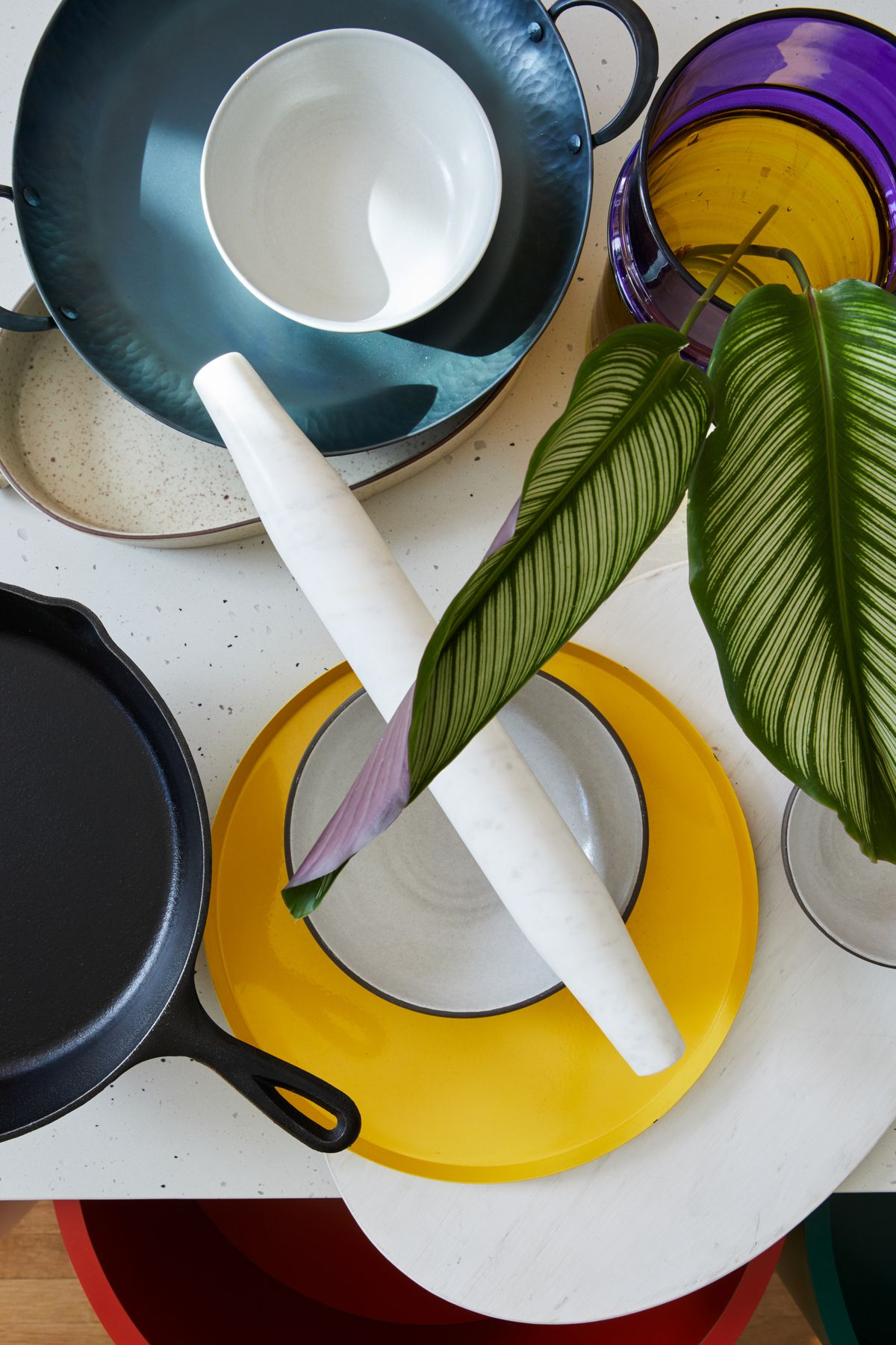 A grouping of kitchen items: a rolling pin, bowls, and a skillet.