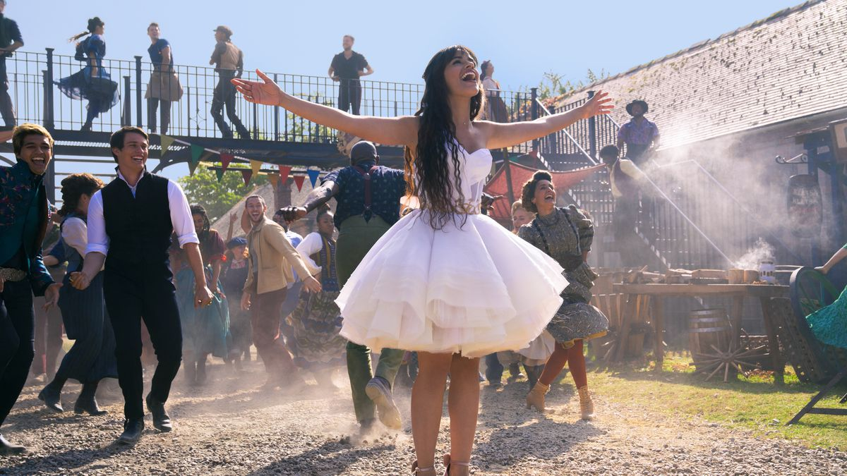 Camila Cabello, in a thigh-length floofy dress, sings outdoors in front of a parade of bland smiling people in Amazon's Cinderella.
