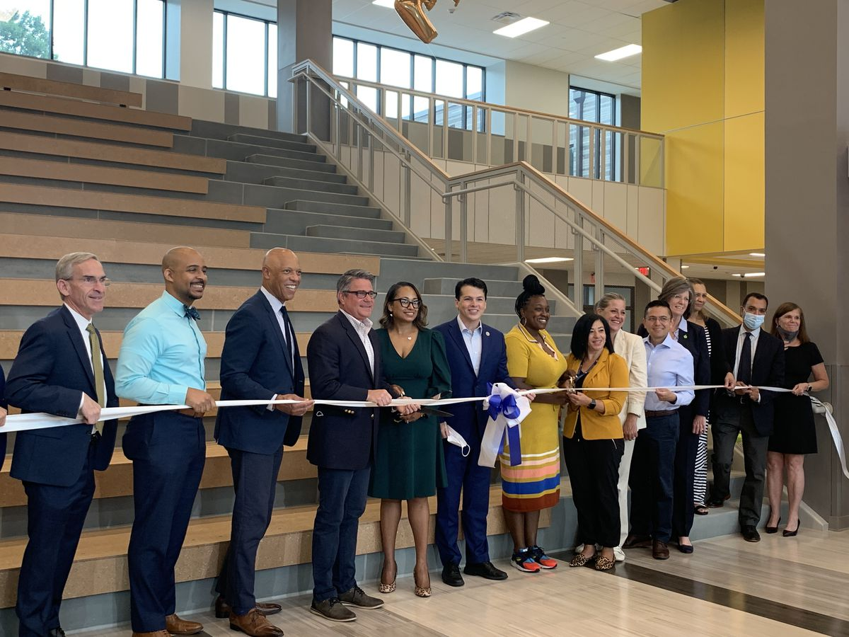 14 people, including School District of Philadelphia Superintendent, pose during a ribbon cutting at Northeast Community Propel Academy.