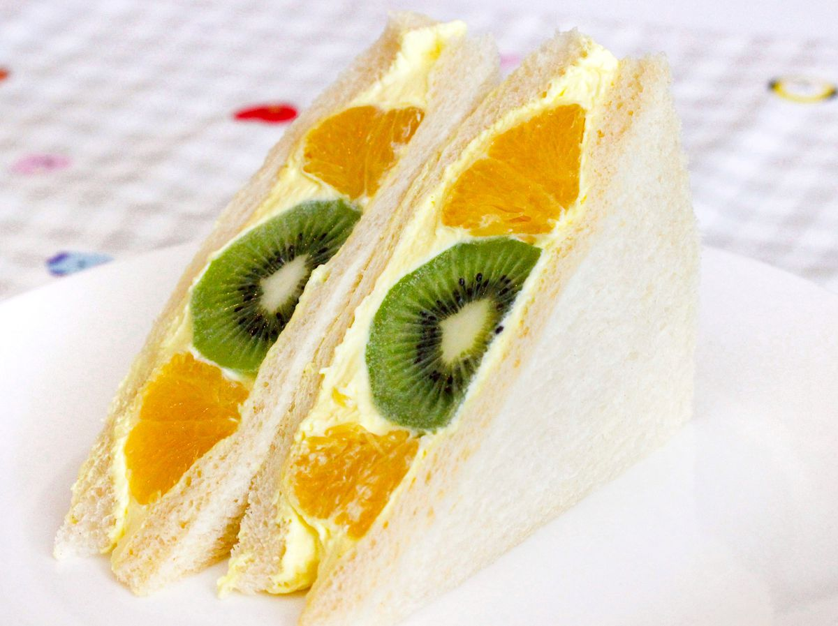 A sandwich, sliced in half, that is filled with yellow whipped cream and slices of kiwi and orange.