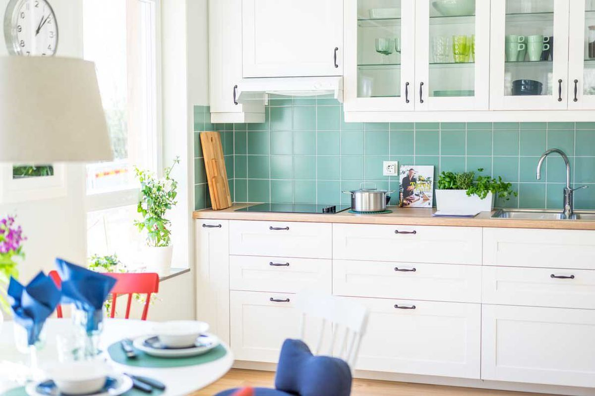 Bright kitchen with green backsplash and white cabinets.
