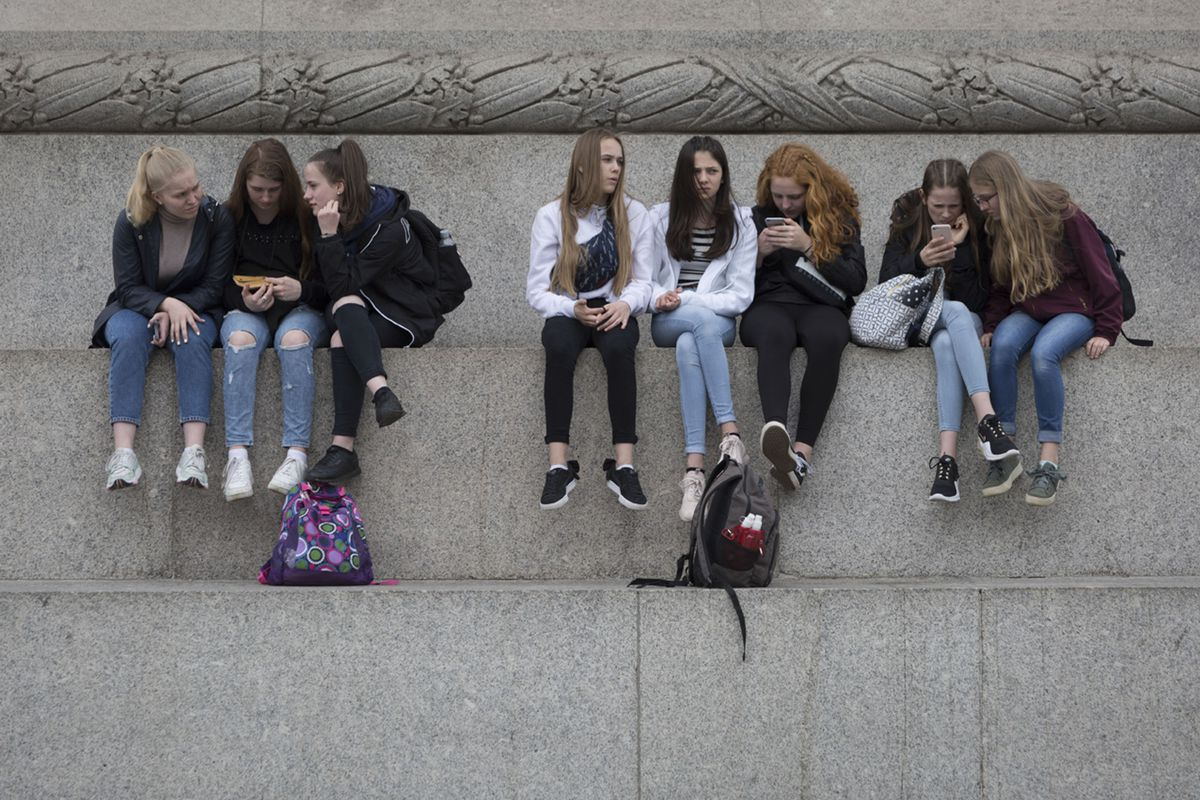 Eight young women sit on a concrete ledge looking at phones.