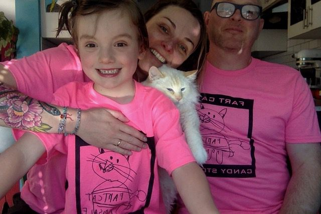 A child, a woman, and a man wear pink shirts that say Fart Cat Candy Store as a white feline looks on.