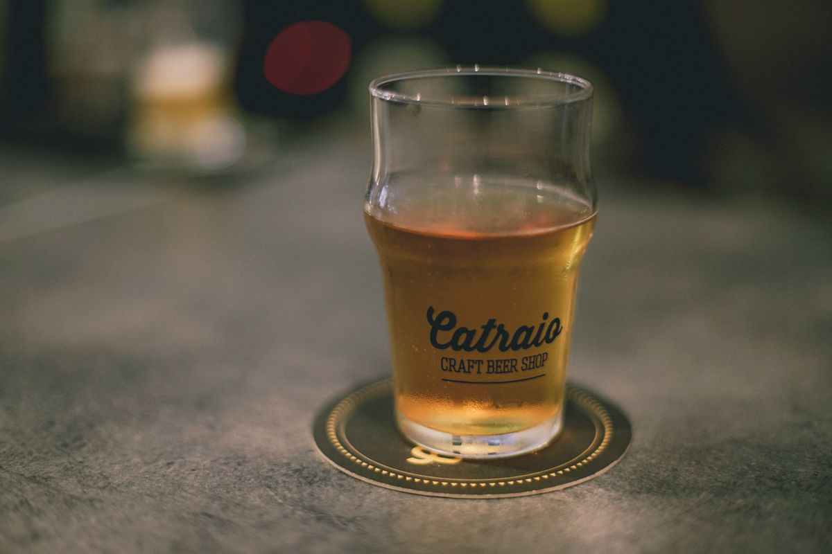 A glass of beer on a coaster on a cement surface with the name of bar Catraio stenciled on the glass