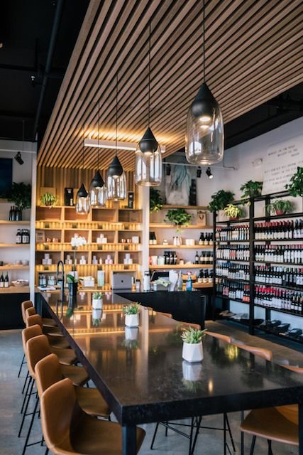 A communal table surrounded by shelves of wine bottles at MRKT SPACE.