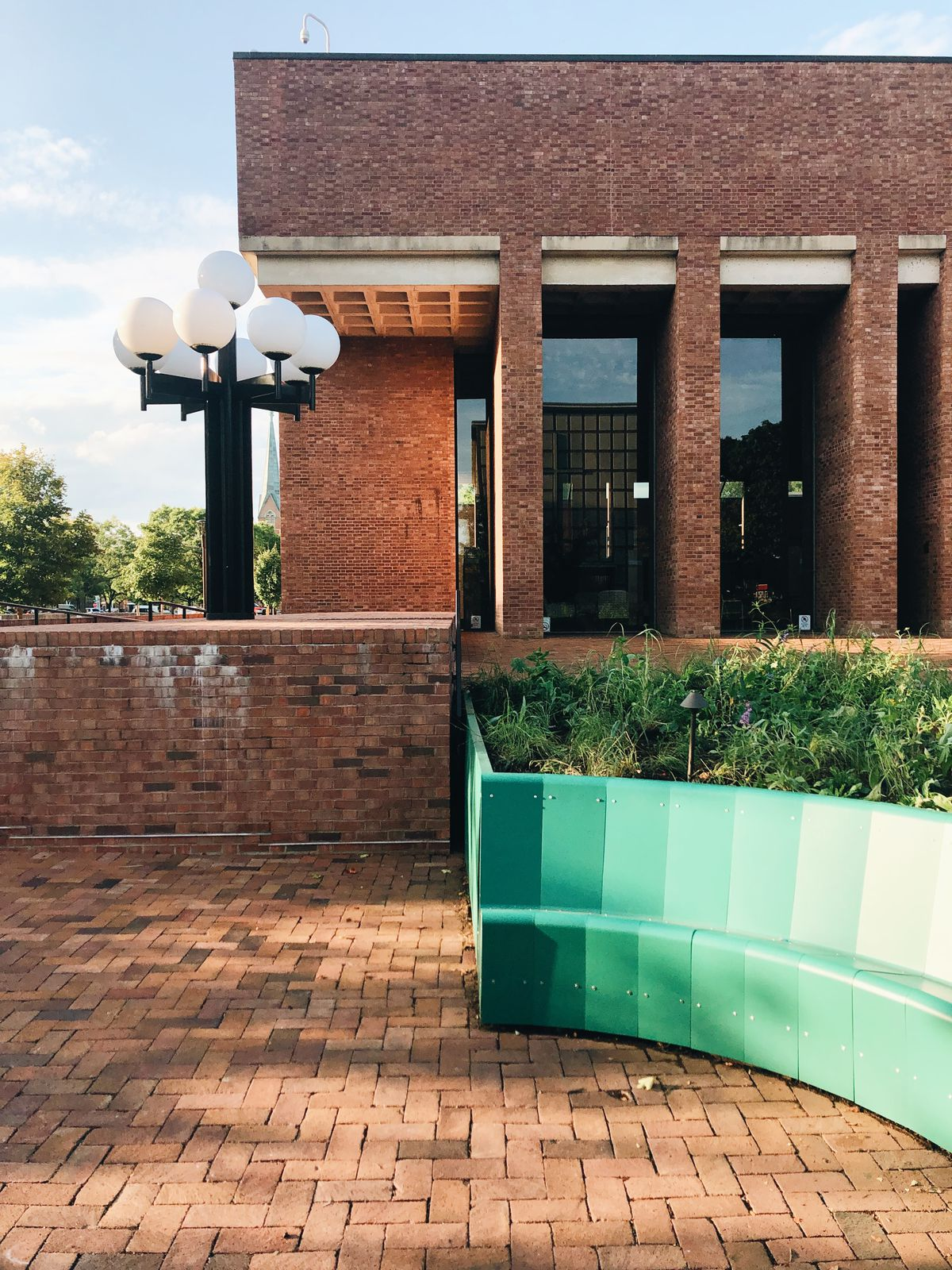 A seating bench designed with different shades of green stands out in the middle of an all-brick building. There is one streetlight and minimal landscaping