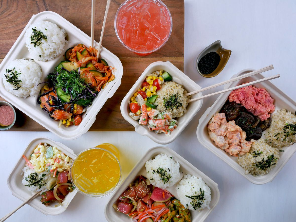 Overhead view of a spread of poke dishes with rice, mac salad, and other accoutrements