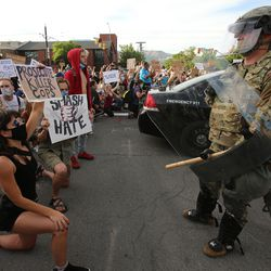 A large group of demonstrators kneel in front of a National Guardsman and police officers between the Salt Lake City Library and the Public Safety Building on Monday, June 1, 2020.