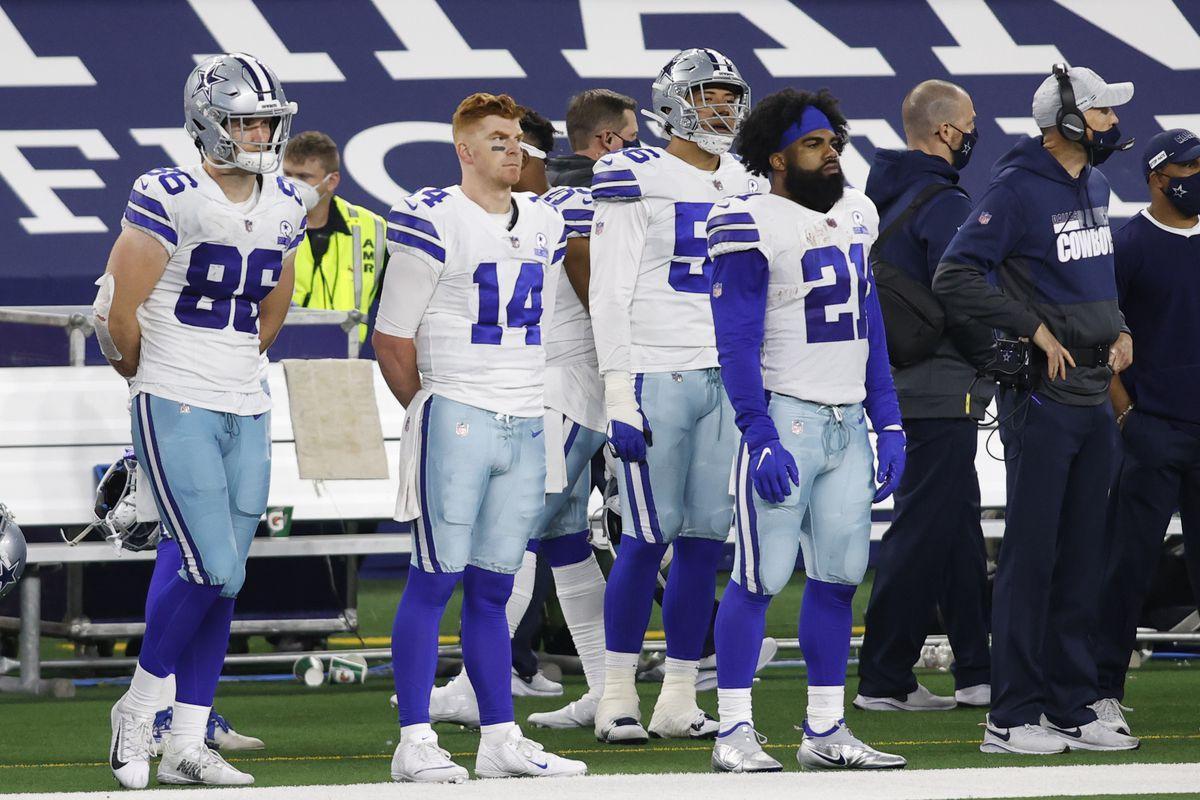 Dallas Cowboys tight end Dalton Schultz (86) and quarterback Andy Dalton (14) and running back Ezekiel Elliott (21) stand on the sidelines during the fourth quarter against the Arizona Cardinals at AT&T Stadium.