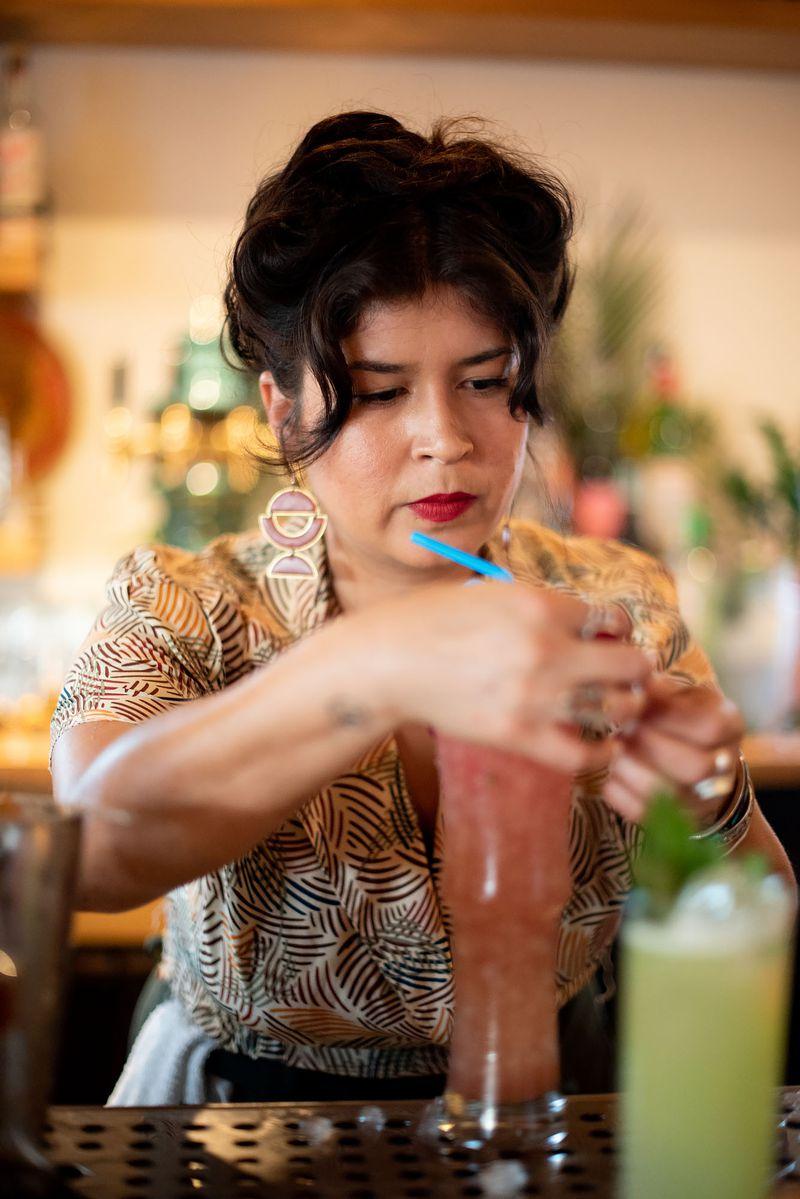 Bartender garnishes a colorful cocktail.