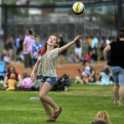Maggie Hyde reaches for a volleyball as she waits during a weather hold at Balloon Fest on Bulldog Field in Provo on Friday, July 2, 2021. The balloons could not fly due to weather but were inflated for display.
