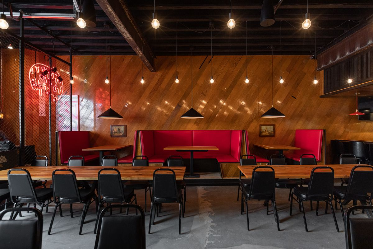 Wood paneled walls are lined with red booths, with long wood tables surrounded by eight chairs each at the center of the dining room.