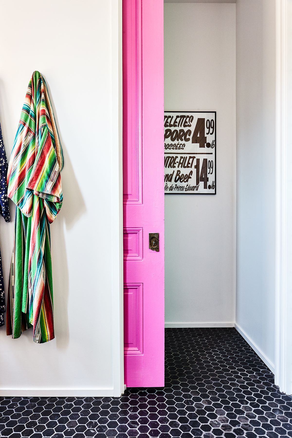 The doorway to a bathroom. The door is bright pink. There is a striped colorful robe hanging on the wall. The floor is tiled in black and white tiles.