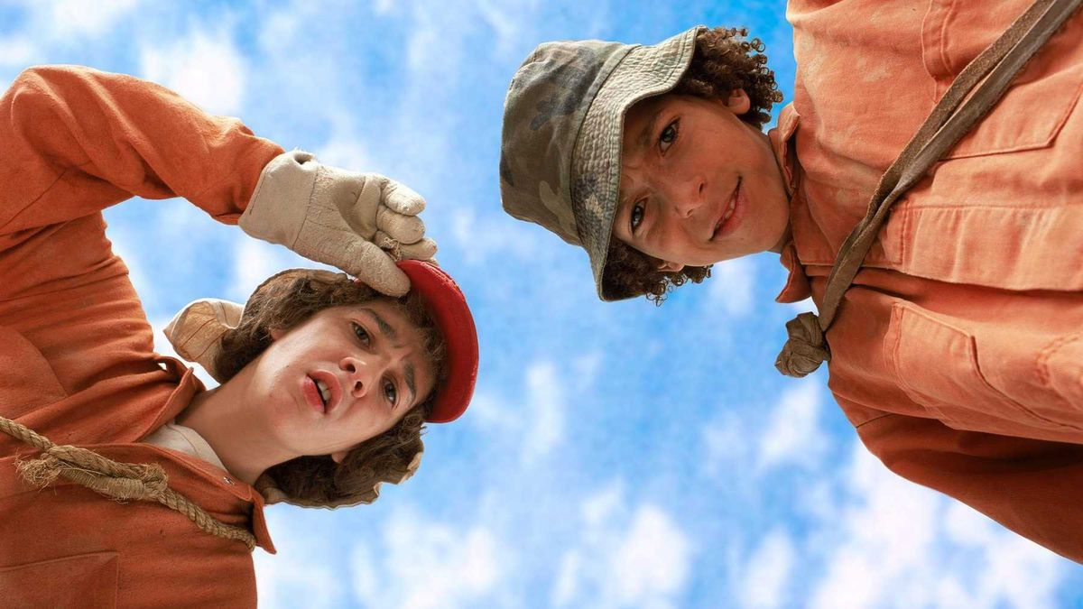 stanley yelnats and zero from Holes, peering down at the viewer. they both wear orange jumpsuits