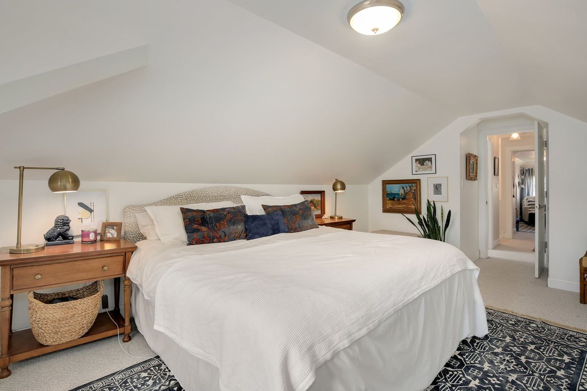 A white platform bed sits against a white wall with wooden nightstands topped with gold globe lamps on either side. There are framed photos and low-light floor plants.