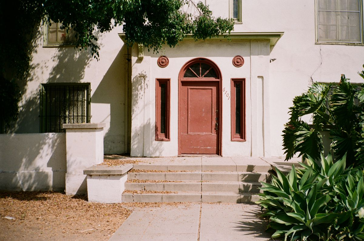The front of an older apartment building, three concrete steps lead up to an off white building, with a red door, rounded at the top, and two long windows on either side, also painted red around the edges. Plants frame the entryway.