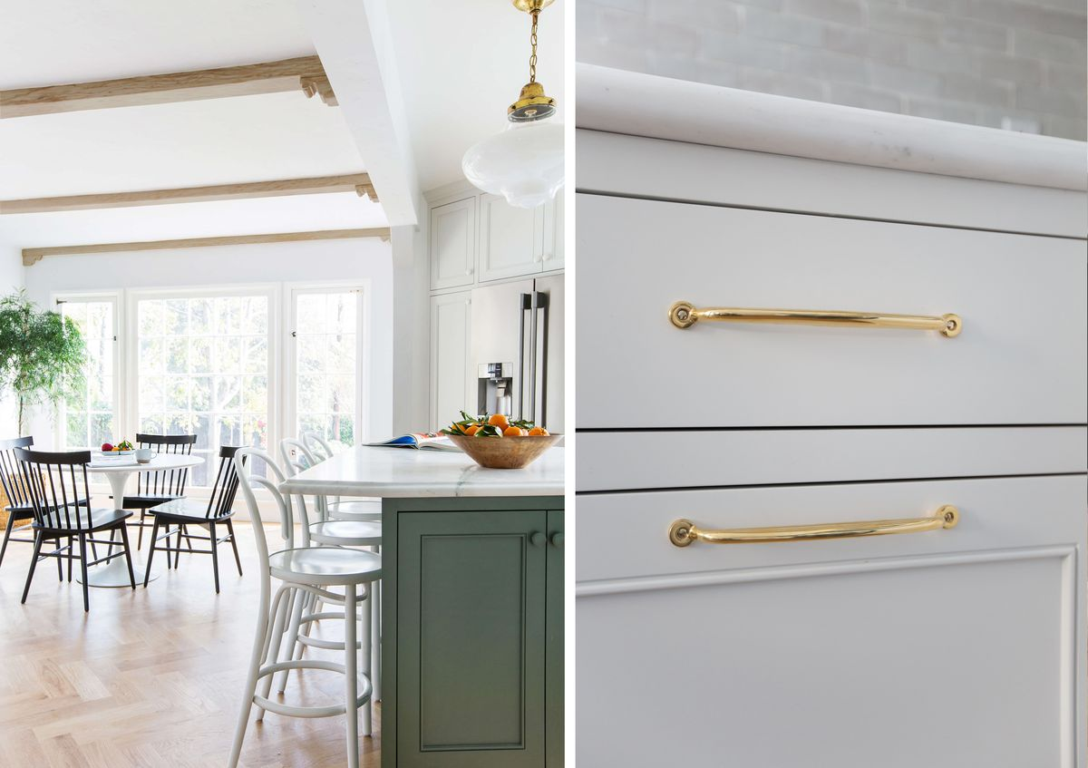 The kitchen opens up to a small table in the dining area. The cabinets are white with long brass handles.