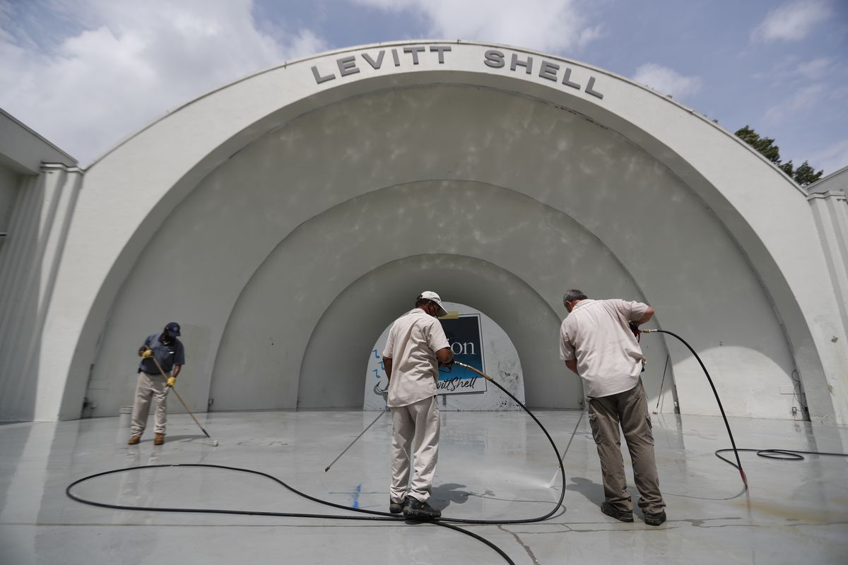 Workers clean graffiti tags off the Levitt Shell Amphitheater after they were discovered Tuesday morning, Sept. 1, 2020, at Overton Park in Memphis, Tenn.