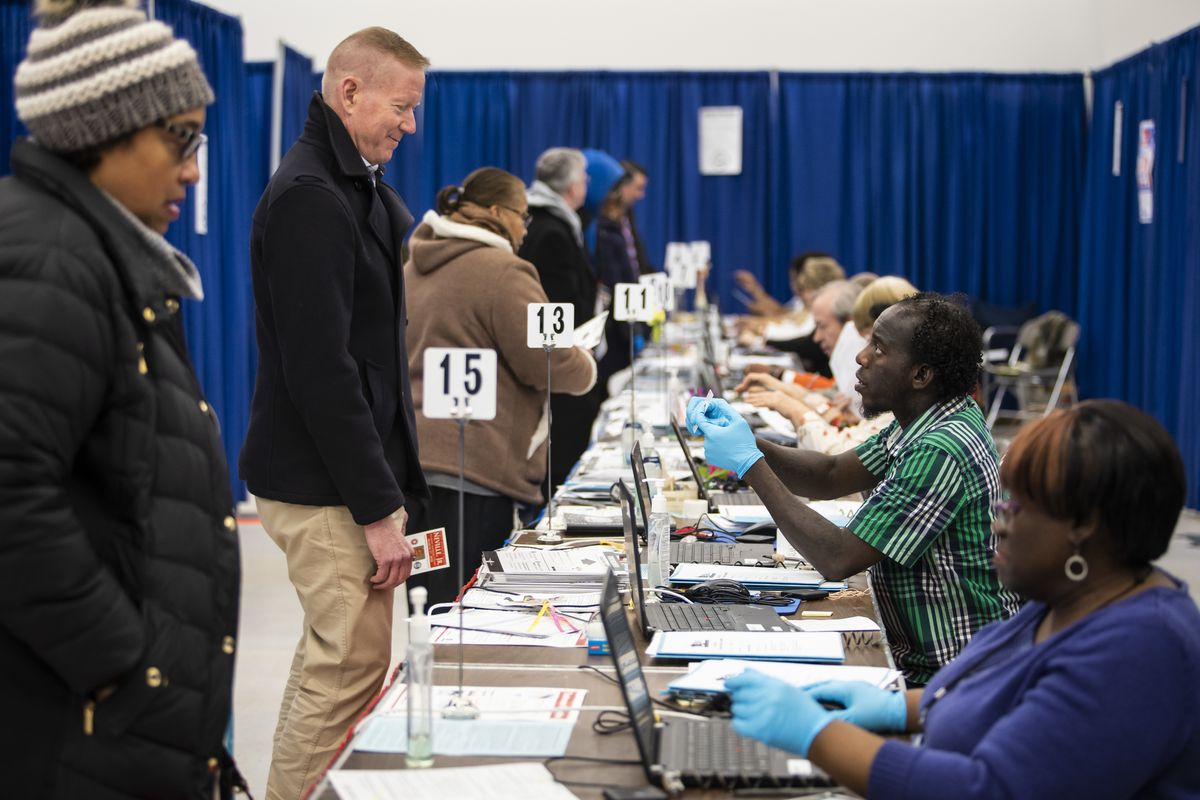 Election officials wear gloves as residents early vote in the March 17 Illinois primary election at the Loop super site at 191 N. Clark St.
