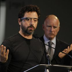 Google co-founder Sergey Brin, left, wearing internet glasses, gestures while speaking as California Gov. Edmund G. Brown Jr., right, listens during a bill signing for driverless cars at Google headquarters in Mountain View, Calif., Tuesday, Sept. 25, 2012.  The legislation will open the way for driverless cars in the state. Google, which has been developing autonomous car technology and lobbying for the legislation has a fleet of driverless cars that has logged more than 300,000 miles (482,780 kilometers) of self-driving on California roads.