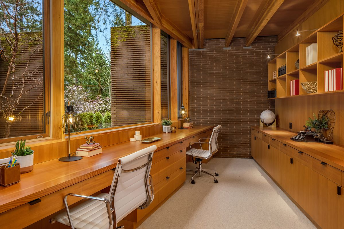 An office with wooden desks, long shelves, and views to the garden.