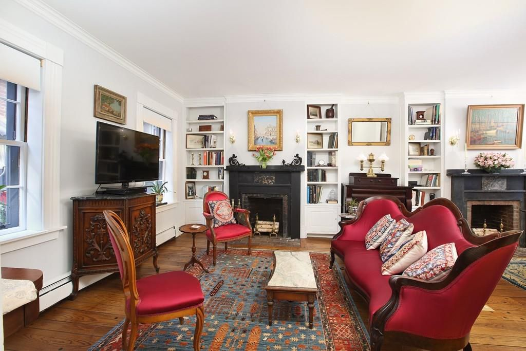 A living room with two couches facing each other and built-in bookshelves at one end.