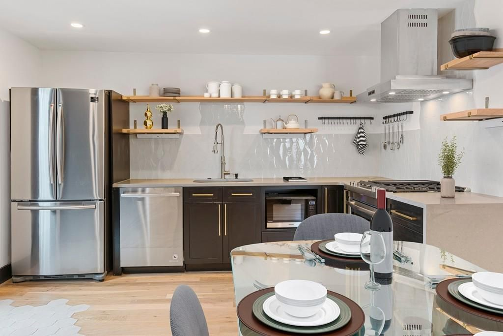 A spacious modern kitchen with a table and chairs in the foreground.