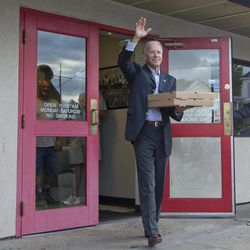 Vice President Joe Biden exits Cardo's Pizza Restaurant with pizza in hand after greeting patrons, Saturday, Sept. 8, 2012, in Jackson, Ohio.