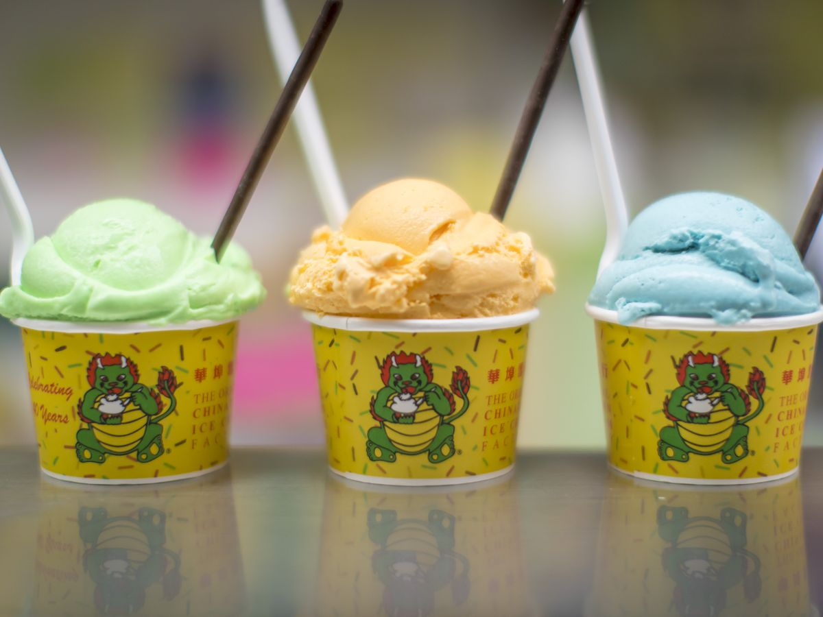 Three yellow cups with green, orange, and blue colored ice cream in them. Each of them have two spoons in them as well.