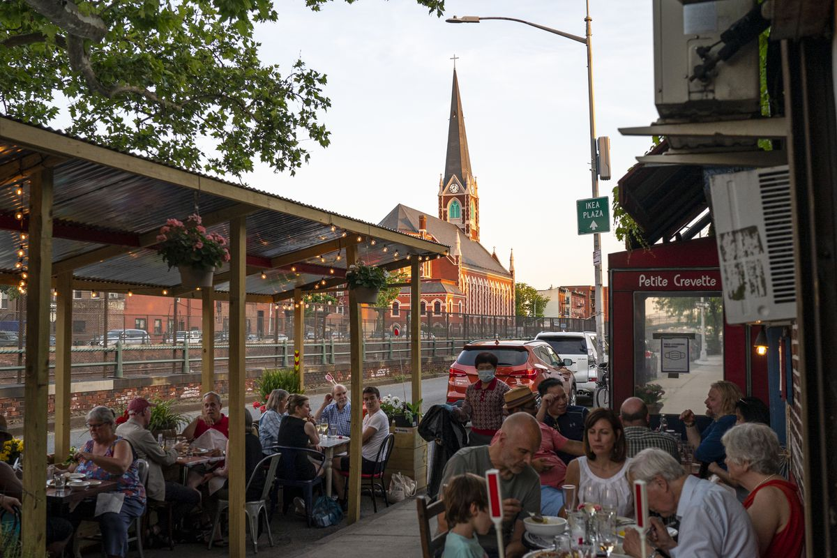 Crowds of people sit outdoors on a summer evening, filling up patio and sidewalk seating at a restaurant in Brooklyn