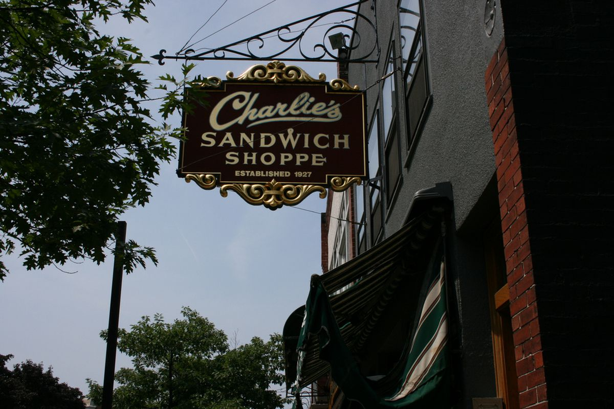 """A sign with gold accents reads """"Charlie's Sandwich Shoppe"""""""