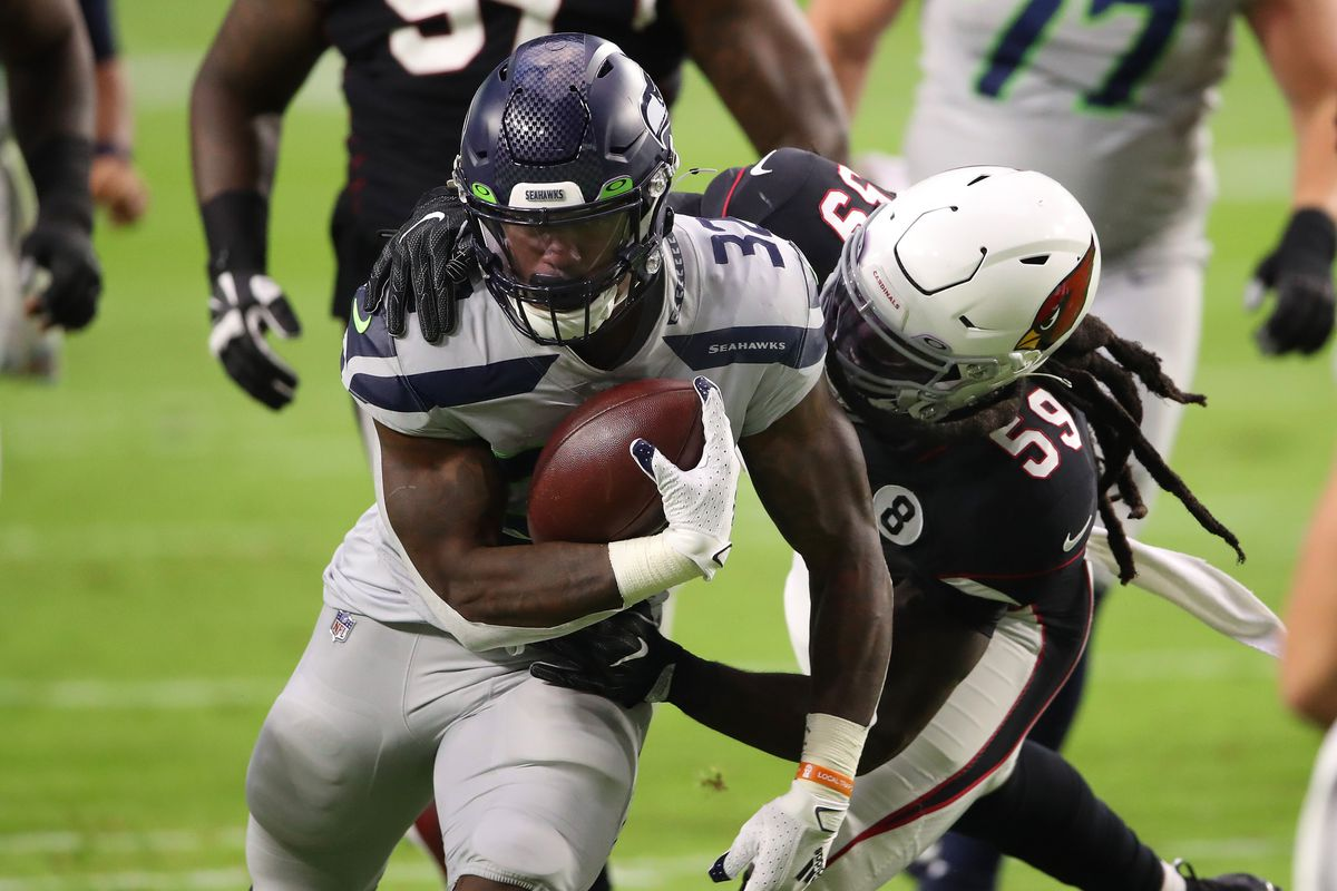 Running back Chris Carson #32 of the Seattle Seahawks runs with the ball after a catch while being tackled by linebacker De'Vondre Campbell #59 of the Arizona Cardinals in the first quarter of the game at State Farm Stadium on October 25, 2020 in Glendale, Arizona.