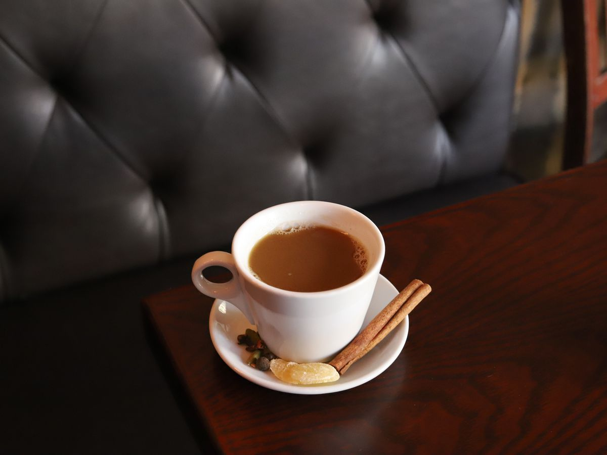A hot cocktail is presented in a white coffee mug on a white saucer, which is embellished with a cinnamon stick. The drink sits on a restaurant table.