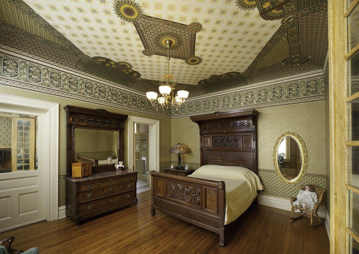 A bedroom features wood floors, a wooden bed and dresser, and gold wallpaper.