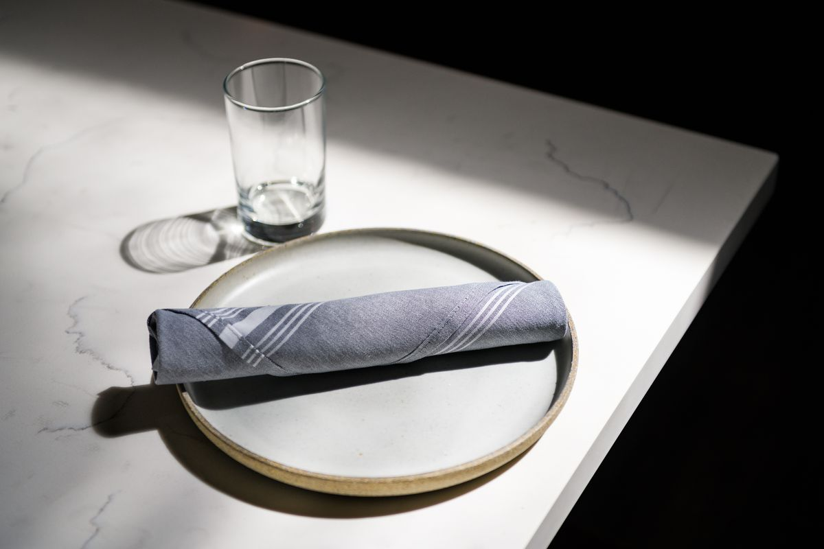 White tables come with cloth napkins and water glasses at Yalla
