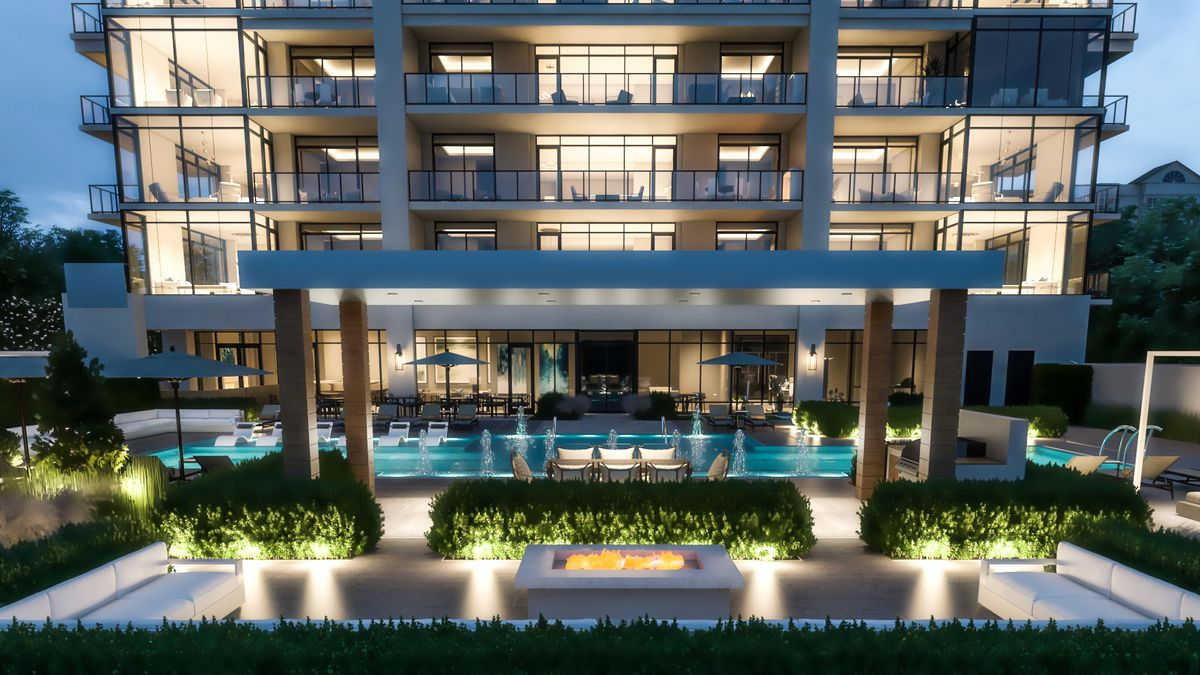 A rendering of a pool and fire pit area at night, around a condo building.