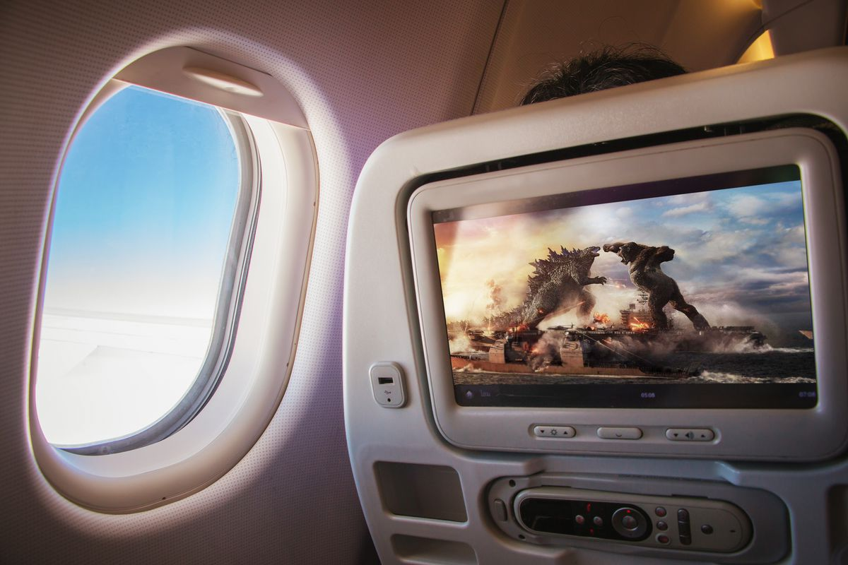 View of plane's cabin windows seat with the movie Godzilla vs. Kong superimposed on the screen