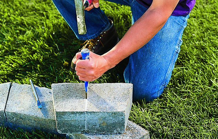 Man Uses Chisel And Brick Hammer To Score Concrete Block On Mark