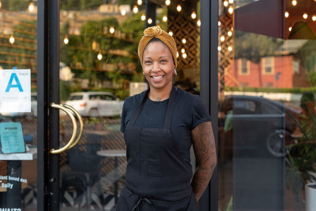 Chef Mimi Williams stands in front of her restaurant wearing a yellow head scarf.