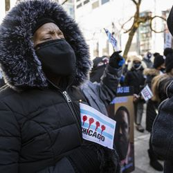 A woman closes her eyes in prayer during a silent protest Thursday on the Magnificent Mile.