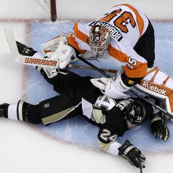 Pittsburgh Penguins' Matt Cooke (24) lies in the goal crease after colliding with Philadelphia Flyers goalie Sergei Bobrovsky during the first period of an NHL hockey game in Pittsburgh Saturday, April 7, 2012. The Penguins won 4-2.