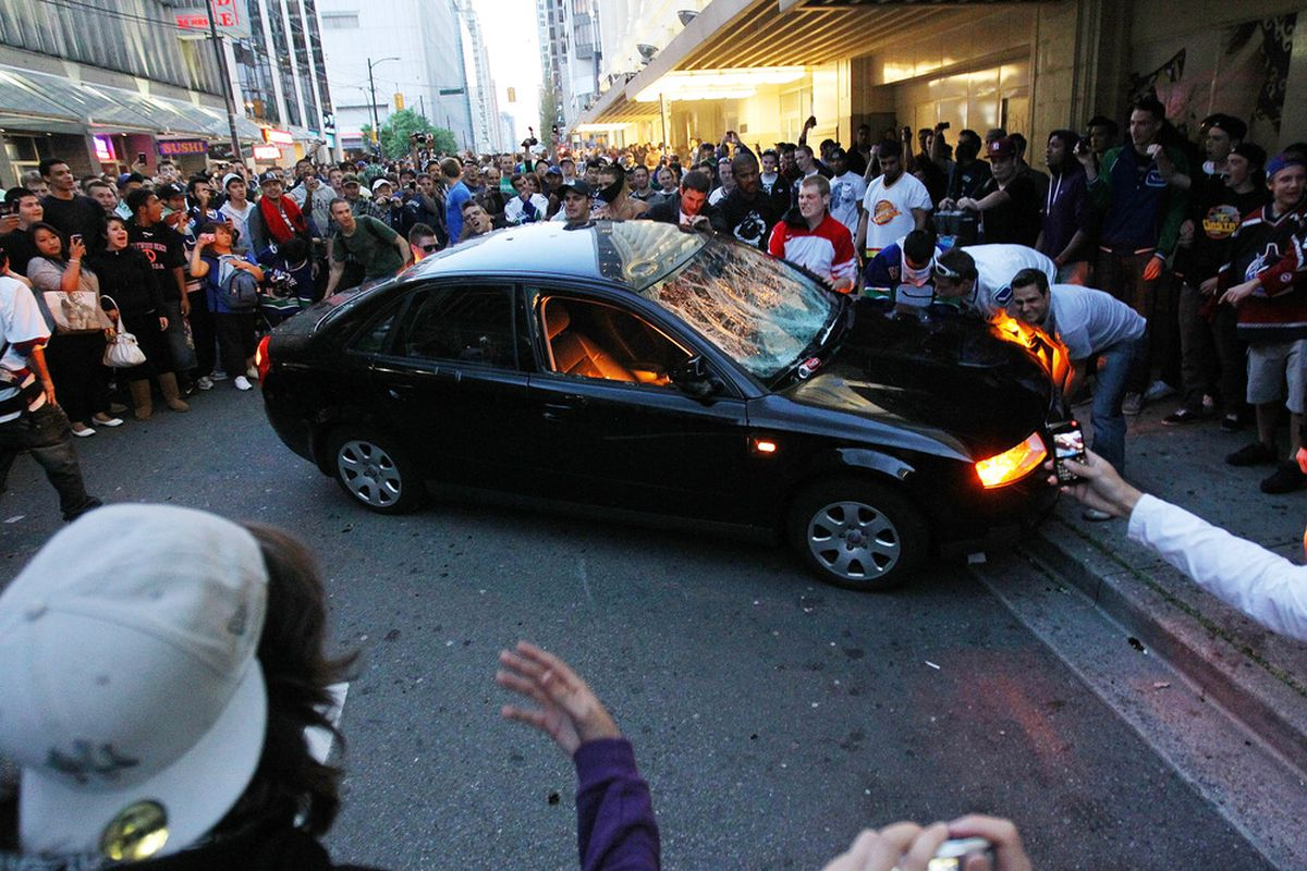 VANCOUVER, BC - JUNE 15:  Rioters try to flip a car on June 15, 2011 in Vancouver, Canada. Vancouver broke out in riots after their hockey team the Vancouver Canucks lost in Game Seven of the Stanley Cup Finals.  (Photo by Bruce Bennett/Getty Images)