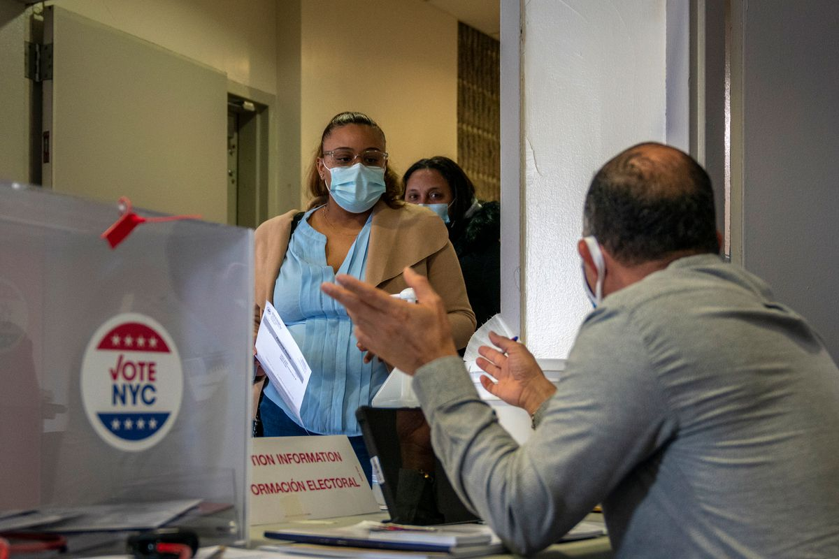 First time Bronx voters Yaritza Liriano, 27, and her mother, Milva Ventura, 46, receive instructions from a poll worker, Nov. 3, 2020.