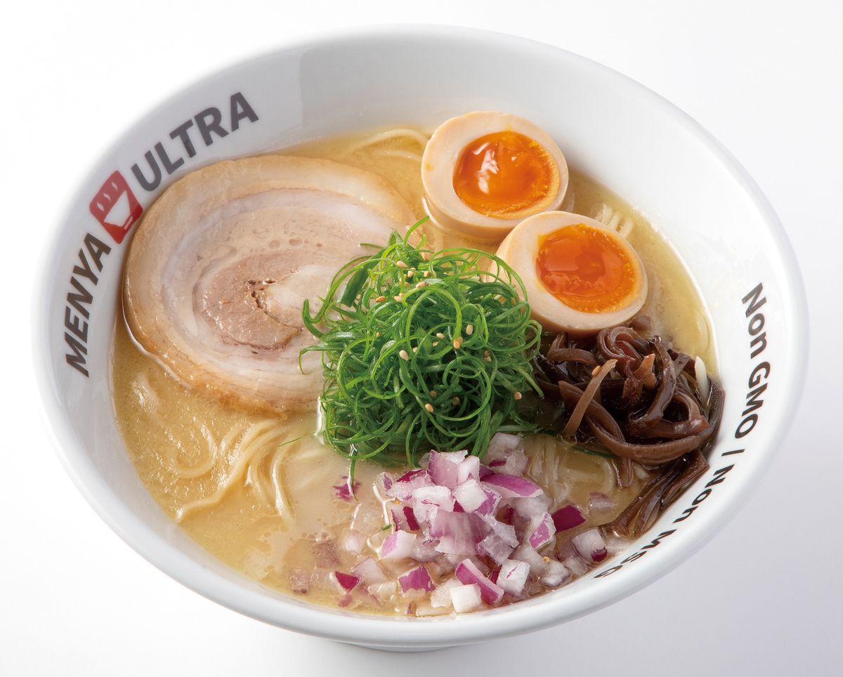 Shio ajitama ramen from Menya Ultra in Hillcrest in a branded white ramen bowl that rests Non GMO Non MSG