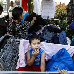 Salima Thapaliya, 3, eats a piece of candy as others line up for clothes and food at the Mosaic Inter-Faith center in Salt Lake City on Thursday, Aug. 4, 2016.