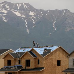 Construction crews work atop the roof of a home being built in Vineyard on Thursday, June 9, 2016.
