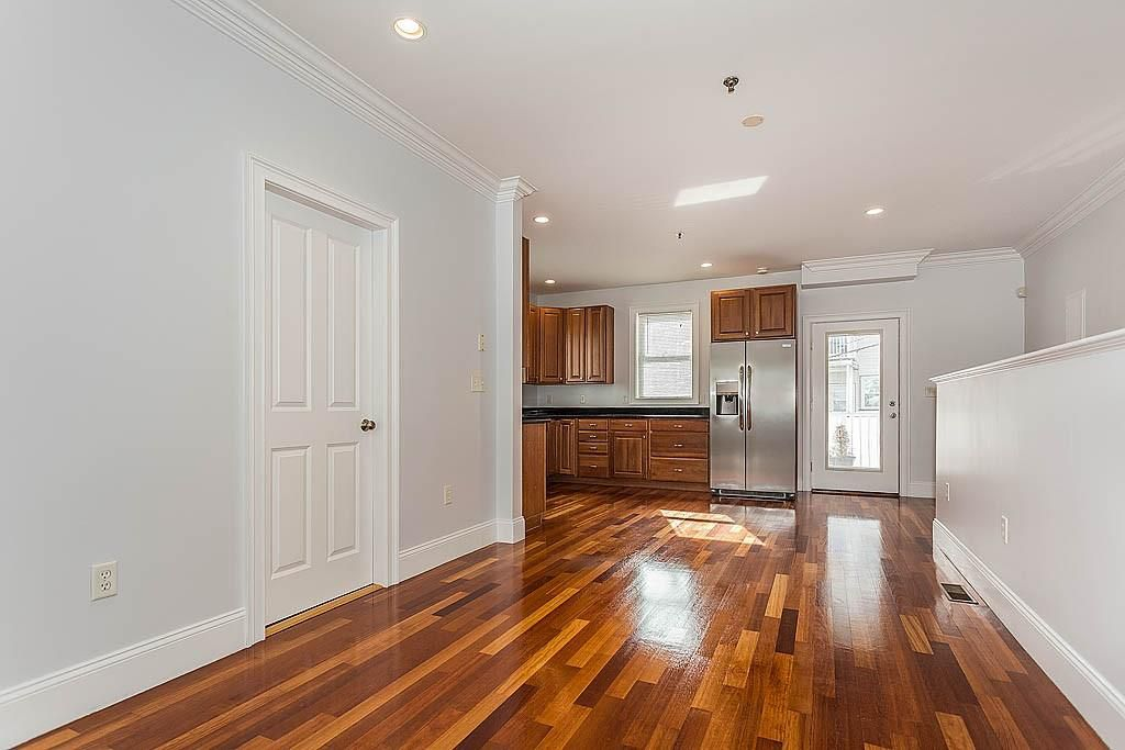 An empty dining room leading into a kitchen in the corner.
