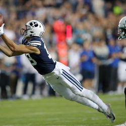 Brigham Young Cougars wide receiver Gunner Romney (18) stretches out for a long pass reception ahead of South Florida Bulls defensive back TJ Robinson (2) as BYU and USF play a college football game at LaVell Edwards Stadium in Provo on Saturday, Sept. 25, 2021.