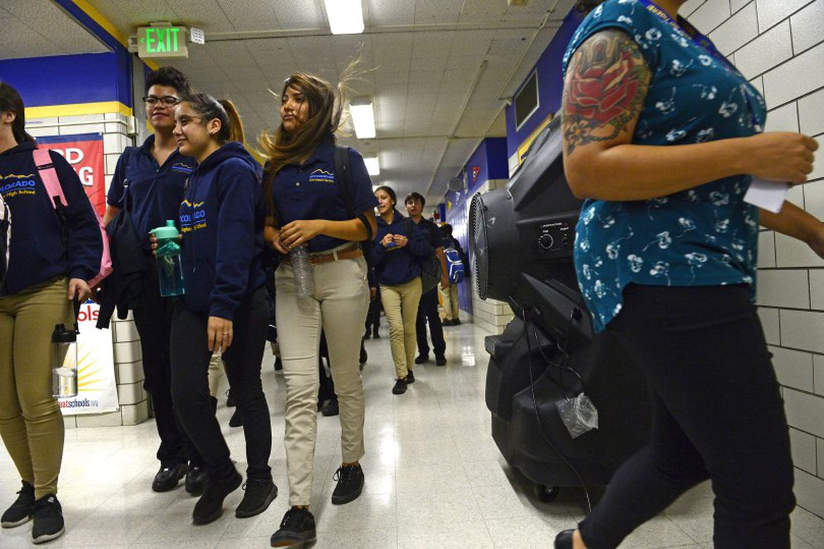 Students walk by large portable cooling systems set up in the hallways of KIPP Denver Collegiate High School in 2018.