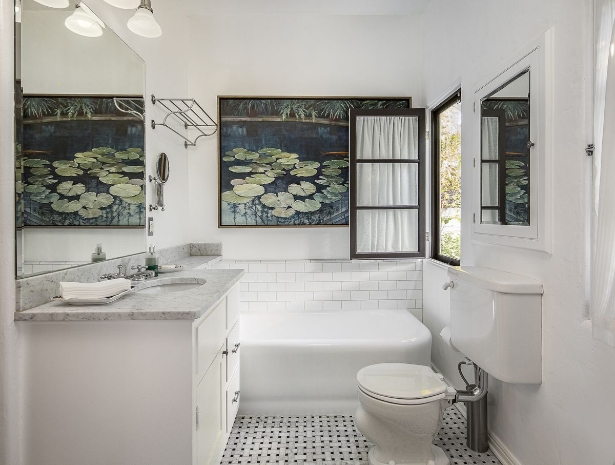 A white tile bathroom with casement windows and a painting of lily pads over the bathtub.